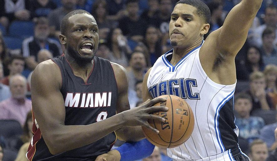 Miami Heat forward Luol Deng (9) drives past Orlando Magic forward Tobias Harris, right, during the first half of an NBA basketball game in Orlando, Fla., Saturday, Dec. 26, 2015. (AP Photo/Phelan M. Ebenhack)