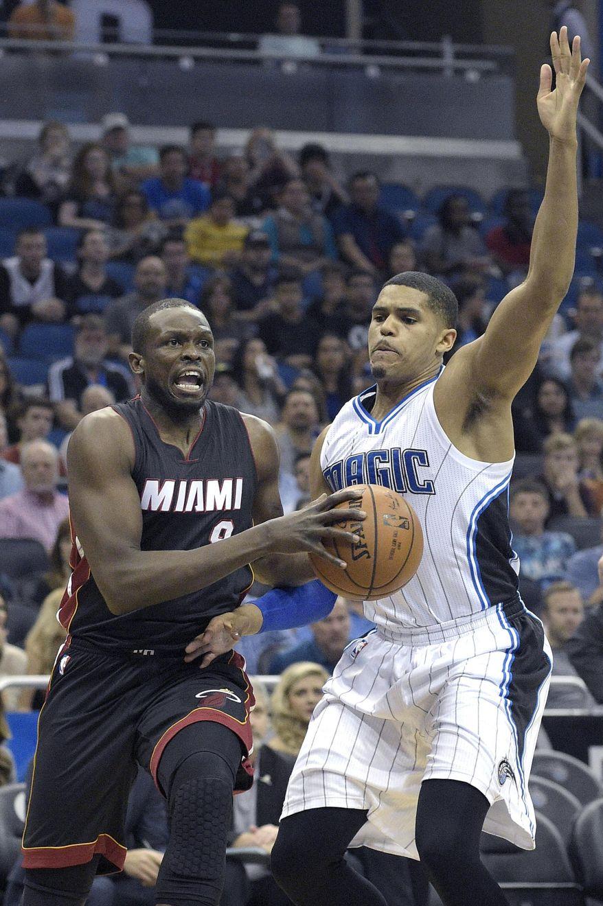 Miami Heat forward Luol Deng (9) drives past Orlando Magic forward Tobias Harris, right, during the first half of an NBA basketball game in Orlando, Fla., Saturday, Dec. 26, 2015. (AP Photo/Phelan M. Ebenhack)