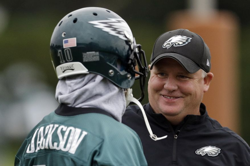 """FILE - In this Sept. 16, 2013, file photo, Philadelphia Eagles wide receiver DeSean Jackson, left, meets with head coach Chip Kelly during practice at the NFL football team's training facility, in Philadelphia. Jackson had his the best season with the Eagles playing under Kelly in 2013. Yet, Kelly cut Jackson a few months after the season. There's one side of the football part of his decision. The other was his contract. But the main reason Jackson was let go was he didn't fit the """"culture"""" Kelly was building in Philadelphia. (AP Photo/Matt Rourke, File)"""