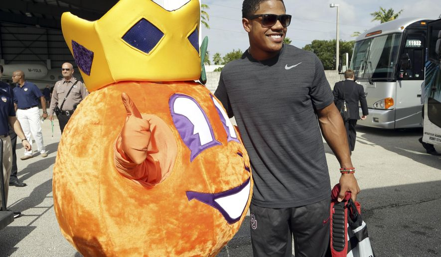 Oklahoma wide receiver Sterling Shepard poses with Obie, the Orange Bowl mascot, after the team arrived in Miami, Saturday, Dec. 26, 2015. Oklahoma plays Clemson in the Orange Bowl NCAA college playoff semifinal Dec. 31 in Miami. (AP Photo/Lynne Sladky)