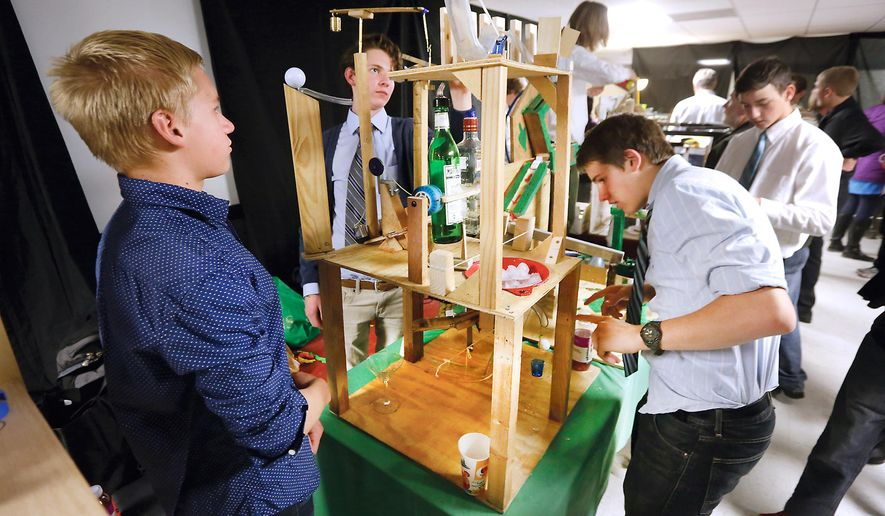 ADVANCE FOR RELEASE SATURDAY, DECEMBER 26, 2015 In this Wednesday, Dec. 9, 2015, photograph, from left, Animas High School students Gus Kidd, 14, Vince Stowers, 14 and Joe Thomson, 15, demonstrate their Rube Goldberg machine that makes a simple task difficult with the end result of making a non-alcoholic martini in Durango, Colo. The students are taking part in a project to encourage creative and complex ways to complete simple tasks in teacher Brian Morgan's physics class. (Jerry McBride/Durango Herald via AP)