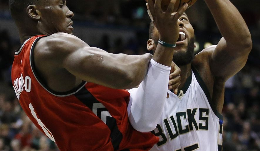 Toronto Raptors' Bismack Biyombo stops Milwaukee Bucks' Greg Monroe (15) during the second half of an NBA basketball game Saturday, Dec. 26, 2015, in Milwaukee. The Raptors won 111-90. (AP Photo/Morry Gash)