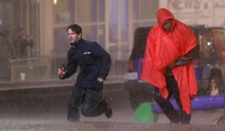 People run as weather sirens sound as a severe storm passes over downtown Dallas, Saturday, Dec. 26, 2015, in Dallas. The National Weather Service said the Dallas area was under a tornado warning Saturday. (AP Photo/LM Otero)