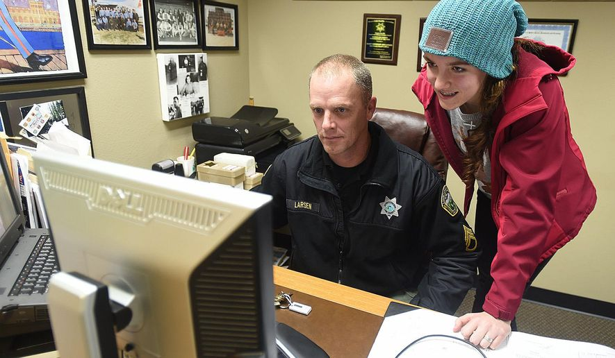 Search and Rescue coofidnator Joe Larsen and Search and Rescue member Savannah Sharpe look through photos at the Linn County Sheriff's Office Wednesday Dec. 16. 2015 in Albany, Ore. (Mark Ylen/Albany Democrat-Herald via AP)