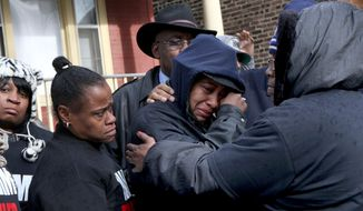 Janet Cooksey, center, the mother of Quintonio LeGrier, is comforted by family and friends during a news conference to speak out about Saturday's shooting death of her son by the Chicago police, on Sunday, Dec. 27, 2015, in Chicago. Grieving relatives and friends of two people shot and killed by Chicago police said Sunday that the city's law enforcement officers had failed its residents. (Nancy Stone/Chicago Tribune via AP) MANDATORY CREDIT