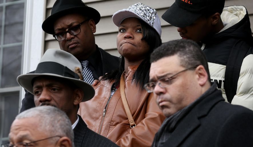 LaTarsha Jones, center, the daughter of Bettie Jones who was shot and killed by Chicago Police, is surrounded by friends and family in front of Jones' home in Chicago on Sunday, Dec. 27, 2015. Attorneys Larry Rogers, Sr., bottom left, and Sam Adam, Jr., bottom right, stand with family members. Grieving relatives and friends of Bettie Jones and a man shot and killed by Chicago police said Sunday that the city's law enforcement officers had failed its residents. (Nancy Stone/Chicago Tribune via AP)