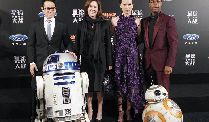 """From left, director J.J. Abrams, producer Kathleen Kennedy, actress Daisy Ridley and actor John Boyega pose with droids character BB-8 and R2-D2 on stage during the premiere of """"Star Wars: The Force Awakens"""" in Shanghai, China, Sunday, Dec. 27, 2015. (Chinatopix via AP) CHINA OUT"""