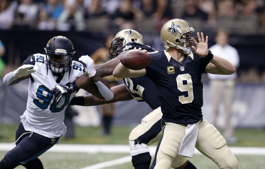 New Orleans Saints quarterback Drew Brees (9) drops back to pass under pressure from Jacksonville Jaguars defensive end Andre Branch (90) in the first half of an NFL football game in New Orleans, Sunday, Dec. 27, 2015. (AP Photo/Jonathan Bachman)