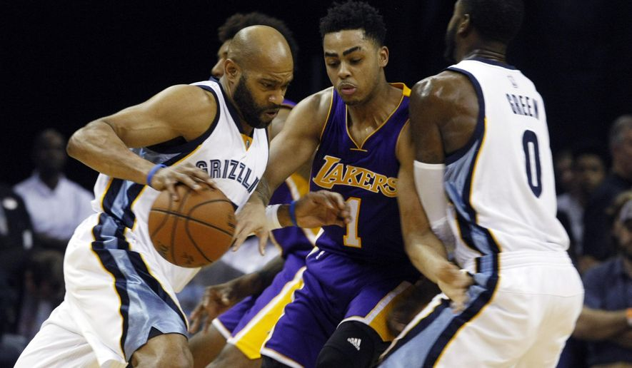 The Grizzlies Vince Carter, left, drives past  Lakers D'Angelo Russell, center, who is screened by JaMychal Green, right, in the first half of an NBA basketball game Sunday, Dec. 27, 2015, in Memphis, Tenn. (AP Photo/Karen Pulfer Focht)