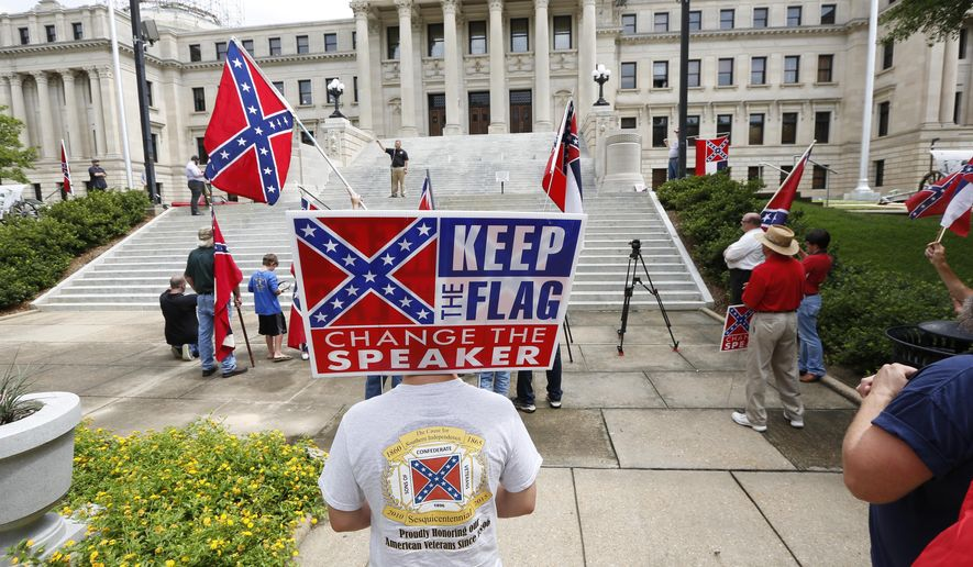 """FILE - In this July 6, 2015, photograph, a small group of Mississippi and Confederate flag-waving citizens participate in a rally sponsored by the Magnolia State Heritage Campaign seeking publicity and support to help keep the Confederate battle emblem in the Mississippi flag on the steps of the Capitol in Jackson, Miss. House Speaker Philip Gunn said his own faith causes him to see the Mississippi flag as """"a point of offense that needs to be removed."""" Several cities and counties, and two universities stopped flying the state flag. Republican Gov. Phil Bryant says he respects results of a 2001 election, when voters chose to keep the Confederate emblem on the flag. However he also said if the issue is going to be revisited, it should happen during the November 2016 election. (AP Photo/Rogelio V. Solis, File)"""