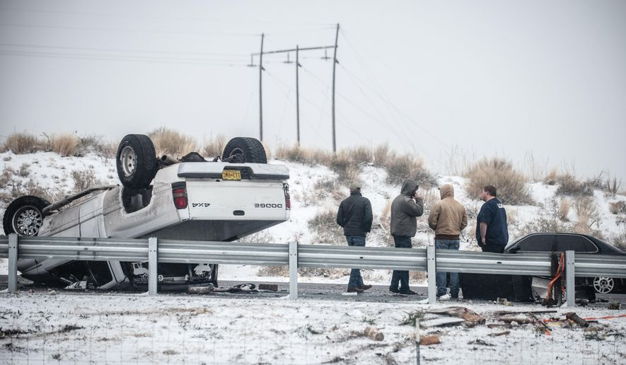 People stand by after a rollover accident along Interstate 25 northbound just south of Albuquerque, N.M., Saturday, Dec. 26, 2015.  A flurry of snow began to blanket Albuquerque, Santa Fe and other cities Saturday afternoon amid warnings of a record-setting blizzard being on the horizon. (Roberto E. Rosales/The Albuquerque Journal via AP) MANDATORY CREDIT