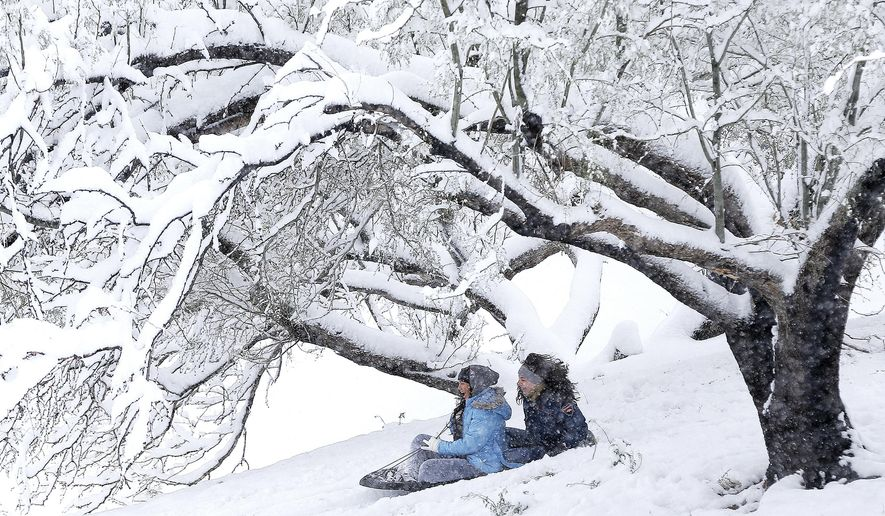 Briana Betancis, 14, and Deziree Dominguez, 12, fly down a hill at Memorial Park in El Paso, Texas, Sunday, Dec. 27, 2015. A heavy snowfall created a winter playground for El Pasoans after several inches remained from an overnight storm. (Mark Lambie/The El Paso Times via AP) MANDATORY CREDIT