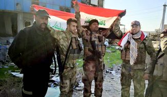 In a strategic and symbolic victory, soldiers raise Iraqi national flags at the government complex in central Ramadi on Monday after retaking it from the Islamic State. Militants occupied the capital of Anbar province since May. (Associated Press)