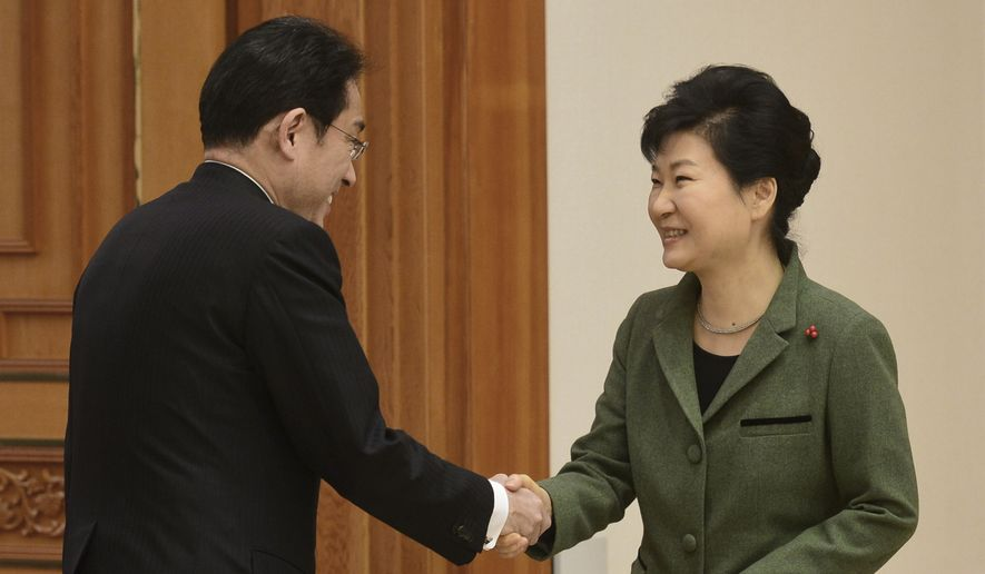 South Korean President Park Geun-hye, right, shakes hands with Japanese Foreign Minister Fumio Kishida prior to a meeting at the presidential house in Seoul, South Korea, Monday, Dec. 28, 2015. The foreign ministers of South Korea and Japan said they had reached a deal meant to resolve a decades-long impasse over Korean women forced into Japanese military-run brothels during World War II, a potentially dramatic breakthrough between the Northeast Asian neighbors and rivals. (Chun Jean-hwan/Newsis via AP) KOREA OUT