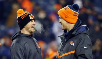 Cincinnati Bengals quarterback Andy Dalton and Denver Broncos quarterback Peyton Manning talk prior to an NFL football game, Monday, Dec. 28, 2015, in Denver. (AP Photo/Jack Dempsey)