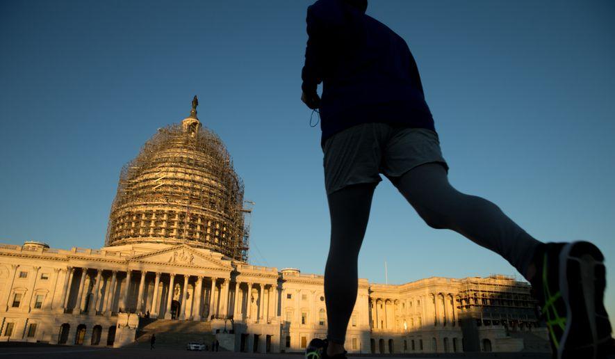 A man jogs past the U.S. Capitol at sunrise in Washington, Saturday, Dec. 19, 2015. (AP Photo/Andrew Harnik)