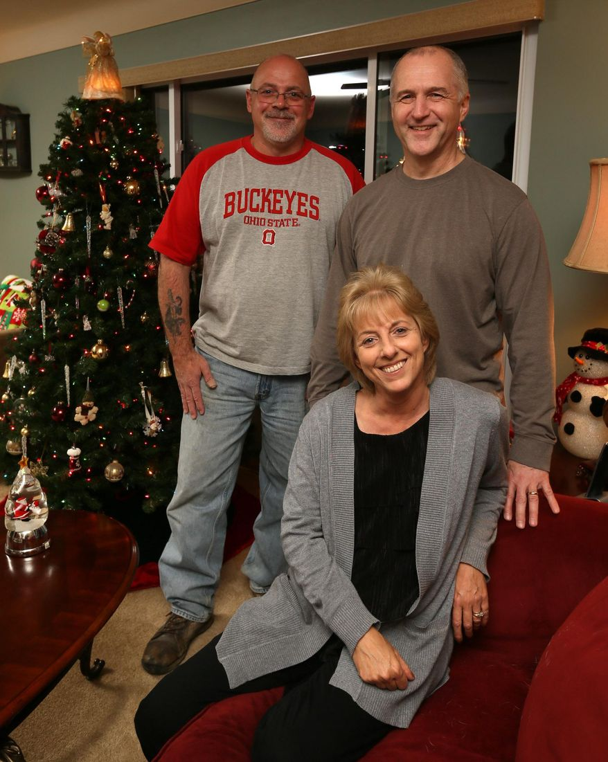 Bob Gondor, left, joins Randy Resh and his wife Traci Grimm at the Resh home on Tuesday, Dec. 22, 2015, in Garfield Heights, Ohio. The two men who say they were wrongfully imprisoned for 16 years for an Ohio woman's 1988 slaying filed for monetary compensation. (Michael Chritton/Akron Beacon Journal via AP)