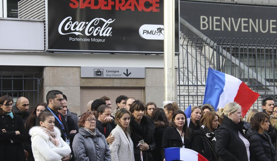 "FILE - This Monday, Nov. 16, 2015 file photo shows people standing for a minute of silence near the Stade de France stadium in Saint Denis, outside Paris. The mother of the youngest of the Paris attackers, who blew himself up outside France's national stadium, says she is ""proud"" that her son killed no one but himself. (AP Photo/Michel Spingler, File)"
