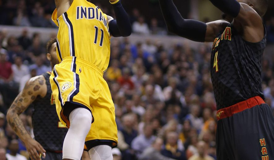 Indiana Pacers guard Monta Ellis, left, shoots over the defense of Atlanta Hawks forward Paul Millsap, right, during the first half of an NBA basketball game in Indianapolis, Monday, Dec. 28, 2015. (AP Photo/AJ Mast)