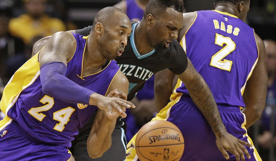 Los Angeles Lakers' Kobe Bryant, left, drives past Charlotte Hornets' P.J. Hairston, right, in the first half of an NBA basketball game in Charlotte, N.C., Monday, Dec. 28, 2015. (AP Photo/Chuck Burton)