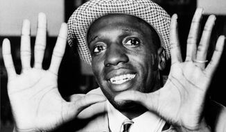 """FILE - In this May 17, 1959, file photo, Meadowlark Lemon, of the Harlem Globetrotters, shows off his large hands on arrival in London where the team was to perform at the Empire Pool in Wembley for a week. Lemon, known as the Globetrotters' """"clown prince"""" of basketball, died Sunday, Dec. 27, 2015, in Scottsdale, Ariz. He was 83. (AP Photo/File)"""