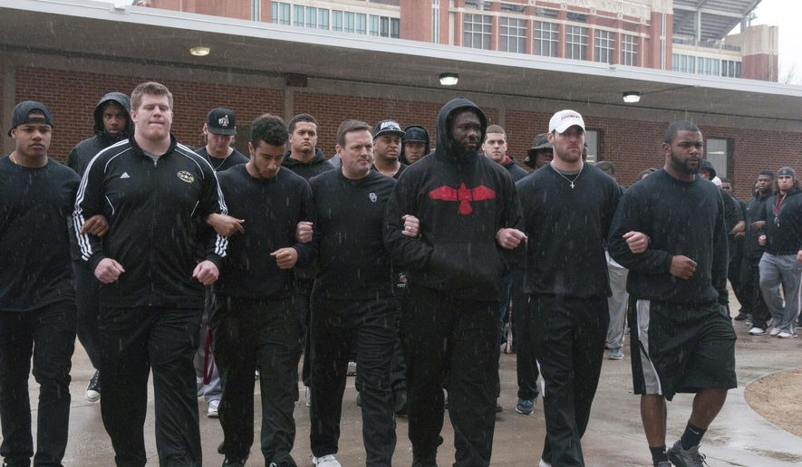 File- This March 9, 2015, file photo shows the University of Oklahoma football team and coaches lining up wearing all black in the Everest Training Center in protest of the Sigma Alpha Epsilon fraternity at the University of Oklahoma. When a racist video shot by members of an Oklahoma fraternity went viral last March, exposing an ugly side to campus life and the isolation that many African-American athletes feel, the football team took a stand. (AP Photo/Tulsa World, Nick Oxford, File)  ONLINE OUT; KOTV OUT; KJRH OUT; KTUL OUT; KOKI OUT; KQCW OUT; KDOR OUT; TULSA OUT; TULSA ONLINE OUT