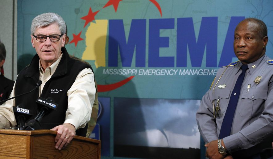Gov. Phil Bryant gives reporters an update on the cleanup efforts from last week's tornadoes outbreak in north Mississippi and a forecast on potential Mississippi River flooding and what officials are expecting, as Mississippi Highway Safety Patrol director Col. Donnell Berry, right, listens, Monday, Dec. 28, 2015 at the Mississippi Emergency Management Agency headquarters in Pearl, Miss. (AP Photo/Rogelio V. Solis)