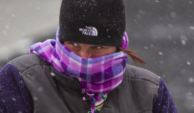 """Casey Sliwa watches family members ice skate in the snow at Rosa Parks Circle in downtown Grand Rapids, Mich., Monday, Dec. 28, 2015. The winter storm is expected to produce hazardous freezing rain and sleet in Lower Michigan this afternoon and evening. Sliwa, who is from Hudsonville, said she plans to """"hunker down"""" at home and watch movies with her family tonight. (Cory Morse/The Grand Rapids Press via AP)"""