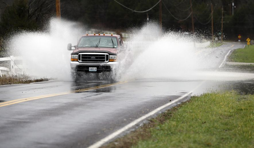 The driver of a pickup truck crosses a flooded section of road Monday, Dec. 28, 2015, in Eureka, Mo. Missouri Gov. Jay Nixon has declared a state of emergency due to wide spread flooding around the state that has closed many roads after a storm system dropped more than half a foot of rain and left several dead. (AP Photo/Jeff Roberson)