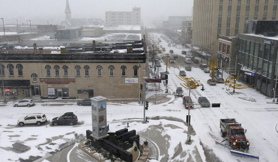 a snowplow leads the way for slow moving traffic monday
