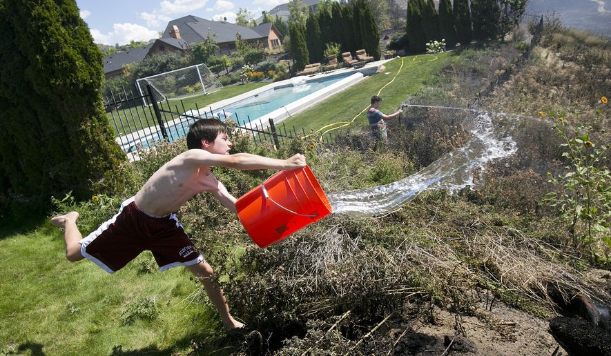 FILE - In this Aug. 13, 2015 file photo, Andrew Fritz, 11, dumps a bucket of water on a smoldering area behind his house located on W. Falcon Crest Court during a fire in the foothills of Boise, Idaho. Wildfire season accelerated in Idaho on Thursday as evacuations were ordered in the northern part of the state and a massive fire straddling the Idaho-Oregon border grew to 340 square miles.  (Kyle Green/Idaho Statesman via AP File)  LOCAL TELEVISION OUT (KTVB 7); MANDATORY CREDIT