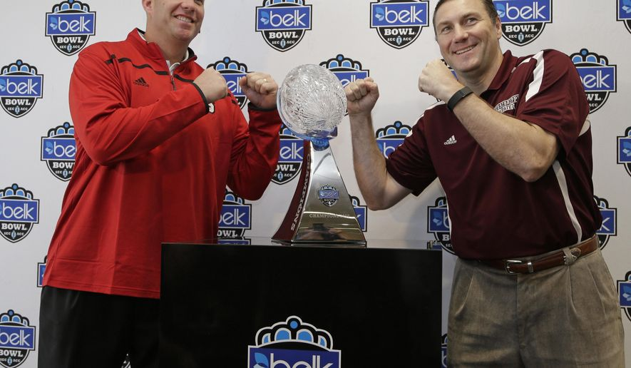 North Carolina State head coach Dave Doeren, left, and Mississippi State head coach Dan Mullen joke as they pose for a photo with the winner's trophy during a news conference for the Belk Bowl NCAA college football game in Charlotte, N.C., Tuesday, Dec. 29, 2015. Mississippi State plays North Carolina State on Wednesday. (AP Photo/Chuck Burton)