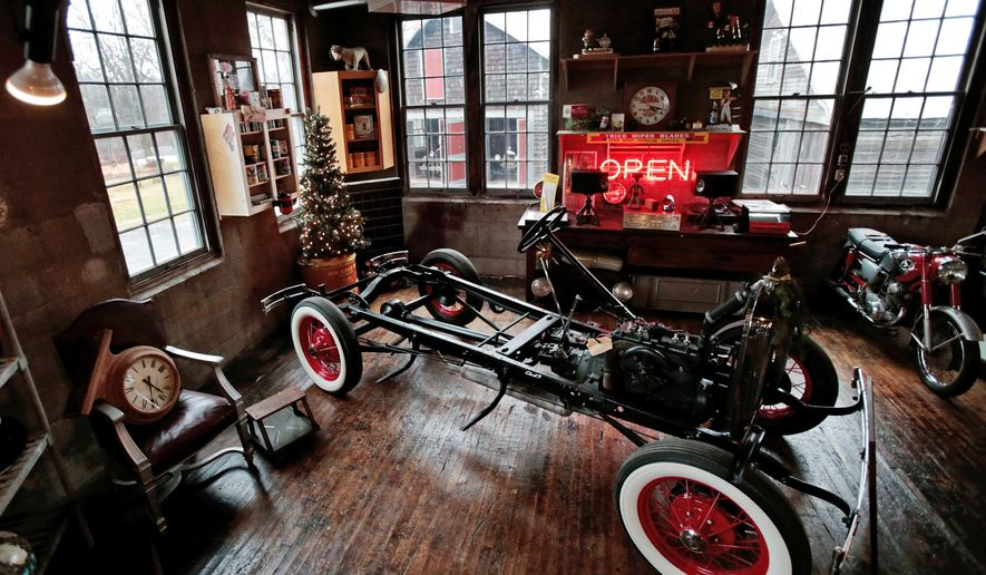 ADVANCE FOR SATURDAY, JAN. 2, 2016- In this photo taken on Tuesday, Dec. 22, 2015, a vintage car frame and other items are displayed at Badger Motor Car Company, a bar and museum in Columbus, Wis. One of the unique draws to the Badger Motor Car Co. is the workshop in the middle of the museum. Visitors can watch as Darvin Frey works on his 1930 Model A pickup truck. (M.P. King /Wisconsin State Journal via AP) MANDATORY CREDIT