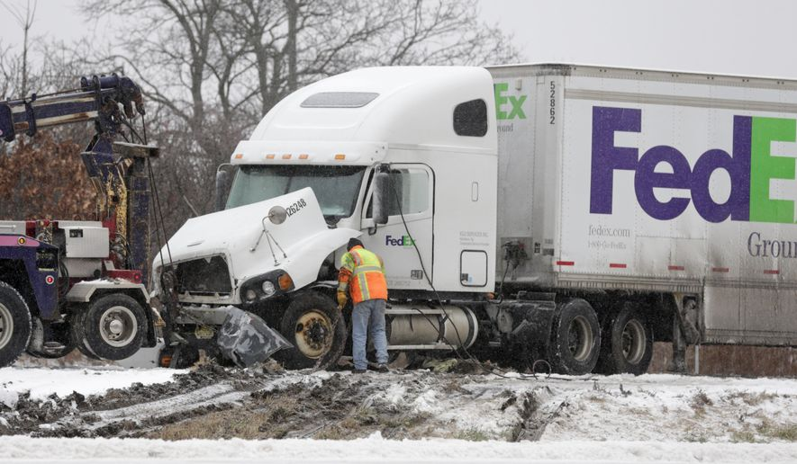 Workers prepare to tow a FedEx tractor-trailer that was involved in an early-morning accident with a passenger vehicle on Interstate 90 on Tuesday, Dec. 29, 2015, in East Greenbush, N.Y. Authorities say a state corrections officer was killed in the crash that shut down most of the highway's lanes east of Albany for hours. The truck driver wasn't injured. Snow and sleet was falling around the time of the accident, and authorities say it's believed the weather conditions were in a factor in the crash. (AP Photo/Mike Groll)
