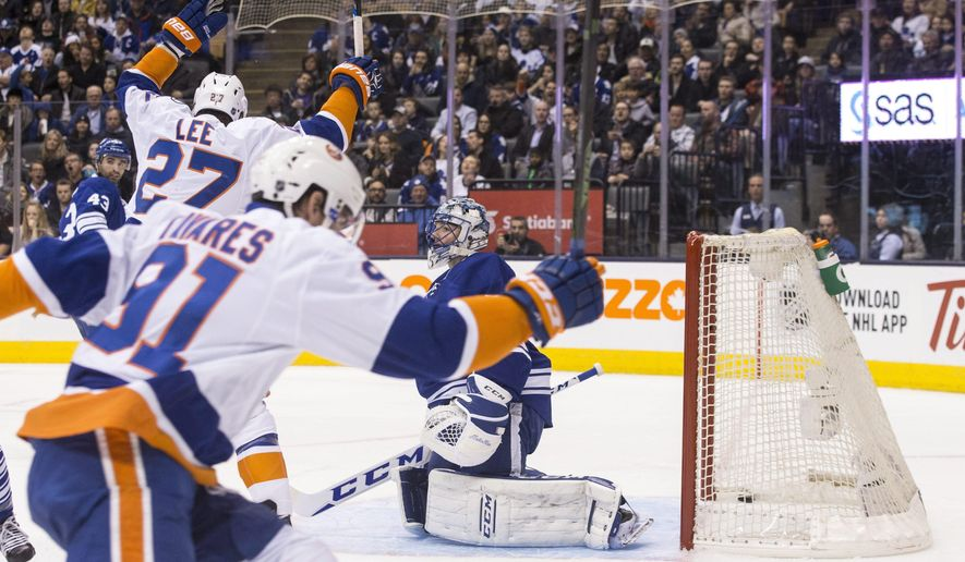 Toronto Maple Leafs' goalie Jonathan Bernier, right, reacts after New York Islanders' John Tavares, front, scores during the first period of an NHL hockey game in Toronto, Tuesday, Dec. 29, 2015.  (Chris Young/The Canadian Press via AP) MANDATORY CREDIT