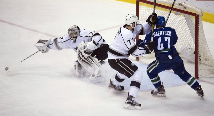 Los Angeles Kings defenseman Derek Forbort (7) tries to clear Vancouver Canucks left wing Sven Baertschi (47) from near Kings goalie Jonathan Quick (32) during the second period of an NHL hockey game Monday, Dec. 28, 2015, in Vancouver, British Columbia. (Jonathan Hayward/The Canadian Press via AP)