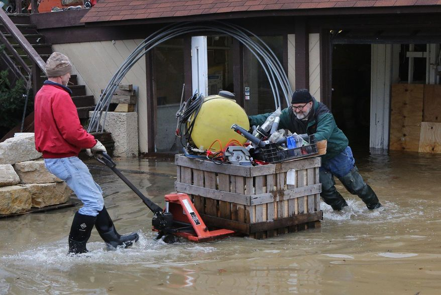 Mark Diehl, left, and Dale Atchley move items to higher ground at the Fenton Feed Mill on Tuesday, Dec. 29, 2015, in Fenton, Mo. Torrential rains over the past several days pushed already swollen rivers and streams to virtually unheard-of heights in parts of Missouri and Illinois. (J.B. Forbes /St. Louis Post-Dispatch via AP)  EDWARDSVILLE INTELLIGENCER OUT; THE ALTON TELEGRAPH OUT; MANDATORY CREDIT
