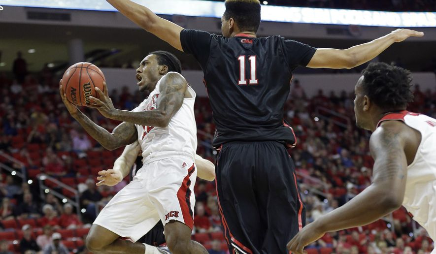 North Carolina State's Anthony Barber drives to the basket as Northeastern's Jeremy Miller (11) defends during the first half of an NCAA college basketball game in Raleigh, N.C., Tuesday, Dec. 29, 2015. (AP Photo/Gerry Broome)