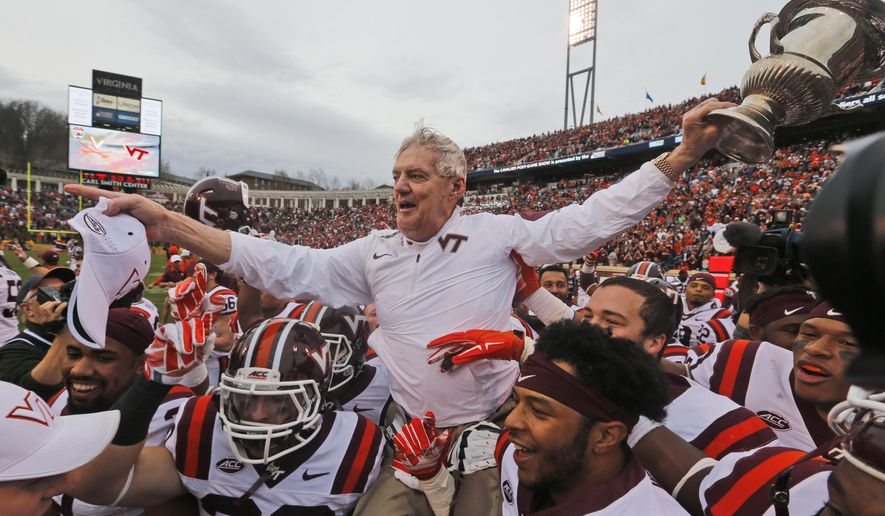 FILE - In this Saturday, Nov. 28, 2015, file photo, Virginia Tech head coach Frank Beamer is carried off the field with the Commonwealth Cup after his team defeated Virginia 23-20 in an NCAA college football game in Charlottesville, Va. Beamer announced his retirement earlier in the season. (AP Photo/Steve Helber, File)