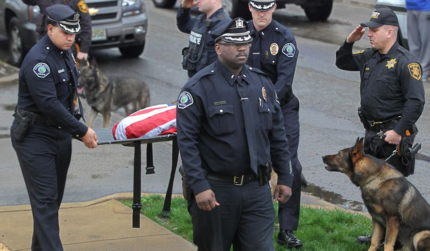 Camden County K-9 officer, Lt. Zsakhiem James, right, walks ahead of the mat carrying his former partner, Zero, wrapped in a flag and held by Lt. Gabriel Rodriguez, left, and Lt. Kevin Lutz, center, as James and Zero were honored by other K-9 units from the South Jersey area,as they walked into the Rothman Animal Hospital on Crescent Blvd Monday, Dec. 28, 2015. The Camden County police department's Officer Zero, the veteran K-9 officer who was Camden's oldest police dog, passed away Monday night at his home, authorities said. (Michael Bryant/Philadelphia Inquirer via AP)