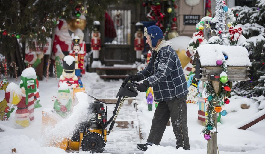 Chris Bowker clears his sidewalk of snow in St. Paul, Minn., on Tuesday, Dec. 29, 2015. The first big snowfall of the year fell overnight and continued into the morning, expecting to accumulate 6 to 9 inches by Tuesday afternoon. (Leila Navidi/Star Tribune via AP)  MANDATORY CREDIT; ST. PAUL PIONEER PRESS OUT; MAGS OUT; TWIN CITIES LOCAL TELEVISION OUT