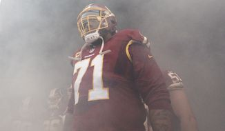 Washington Redskins tackle Trent Williams (71) stands in the smoke waiting for his introduction before an NFL football game against the New York Giants in Landover, Md., Sunday, Nov. 29, 2015. (AP Photo/Mark Tenally)