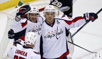 Washington Capitals' John Carlson (74) celebrates his goal with teammates Jay Beagle (83), and Jason Chimera (25) during the first period of an NHL hockey game against the Pittsburgh Penguins in Pittsburgh Monday, Dec. 14, 2015.(AP Photo/Gene J. Puskar)