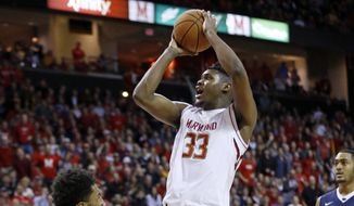 Maryland center Diamond Stone, center, shoots over Penn State guard Josh Reaves in the second half of an NCAA college basketball game, Wednesday, Dec. 30, 2015, in College Park, Md. Stone contributed a game-high 39 points to Maryland's 70-64 win. (AP Photo/Patrick Semansky)