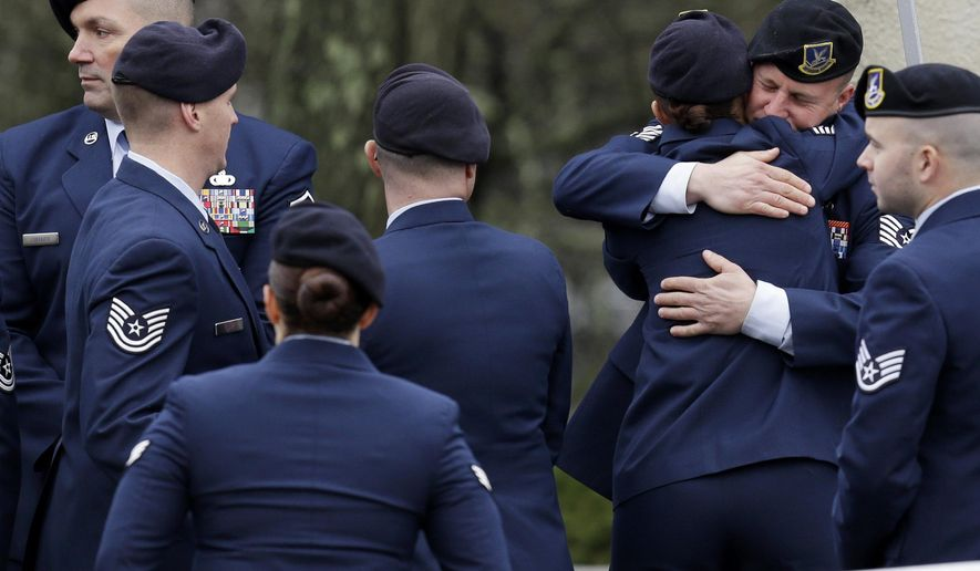 Service members embrace while waiting to enter the wake for Joseph Lemm in West Harrison, N.Y., Tuesday, Dec. 29, 2015. Lemm, who was a technical sergeant in the Air Guard's 105th Base Security Squadron and a 15-year veteran of the NYPD, was killed on Dec. 21 when his patrol was attacked by a suicide bomber outside Bagram Air Base in Afghanistan. (AP Photo/Seth Wenig)
