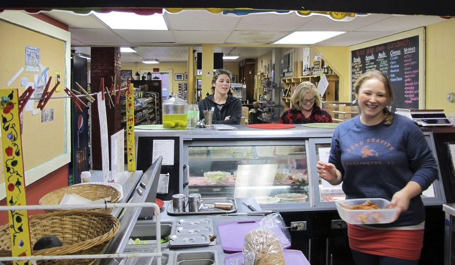 In this Dec. 18, 2015 photo, Becca Turner, right, works in the deli as Shanely and Catherine Tarrant await their order at the Underhill Country Store in Underhill, Vt. The 130-year-old store, a community hub, was at risk of closing after the owners decided to retire but had trouble selling it. The community rallied, raising just over $39,000 in four days to save the store. (AP Photo/Lisa Rathke)