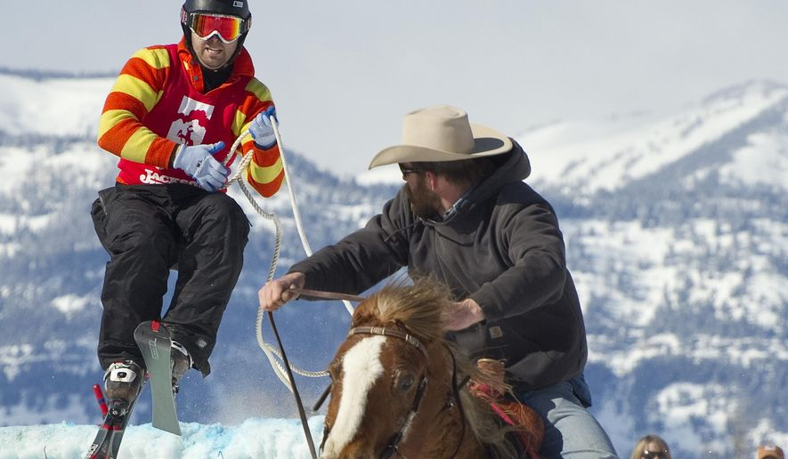 Team Batman and Robin (Robin is the horse) put on a good show as skier Barton Slamey pulls in some rope coming off the second jump. With Brandon Whittington in the saddle, the skijoring team posted a time of 19.6 seconds back in 2013. (Price Chambers/Jackson Hole News and Guide via AP)