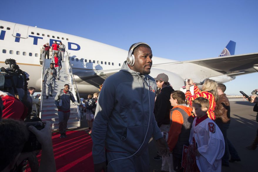 Ohio State quarterback Cardale Jones, center, and teammates disembark after arriving at an airport in Phoenix on Sunday, Dec. 27, 2015. Ohio State is scheduled to play Notre Dame in the Fiesta Bowl on New Year's Day. (Cheryl Evans/The Arizona Republic via AP)