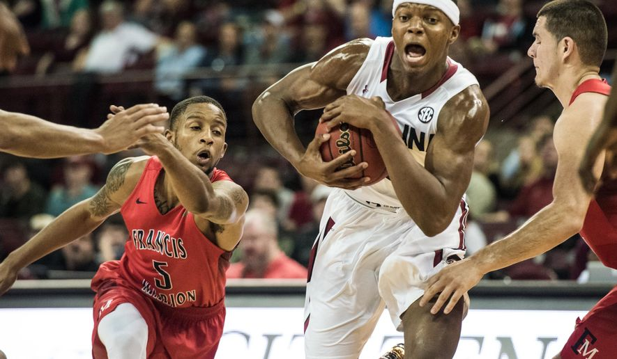 South Carolina guard Temarcus Blanton, center, drives to the basket between Francis Marion's Alante Fenner (5) and Nick Talko, right, during the second half of an NCAA college basketball game on Wednesday, Dec. 30, 2015, in Columbia, S.C. South Carolina defeated Francis Marion 78-56. (AP Photo/Sean Rayford)