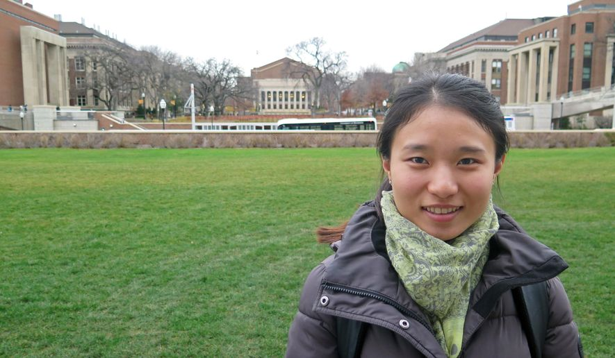 In this photo taken on Nov. 21, 2015, Sai Wang, a junior at the University of Minnesota who transferred from a school in China, poses on campus, in Minneapolis. Wang said she came to study in the U.S. because of the value of an American diploma. She is among nearly 7,000 international students at the university, a number that's doubled over the last decade. (Peter Cox /Minnesota Public Radio via AP) MANDATORY CREDIT